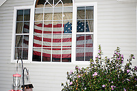 """An American flag hangs in a house window while Texas senator and Republican presidential candidate Ted Cruz speaks to attendees at an event called """"Smoke a cigar with Ted Cruz"""" at a house party at the home of Linda & Steven Goddu Salem, New Hampshire."""