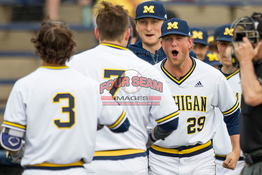 Michigan Wolverines pitcher Mac Lozer (29) greets teammate Harrison Wenson (7) after his 8th inning home run against the Toledo Rockets on April 20, 2016 at Ray Fisher Stadium in Ann Arbor, Michigan. Michigan defeated Bowling Green 2-1. (Andrew Woolley/Four Seam Images)