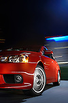 Motion photo of a 2009 Mitsubishi Lancer Evolution MR driving with urban city light blurred in background.
