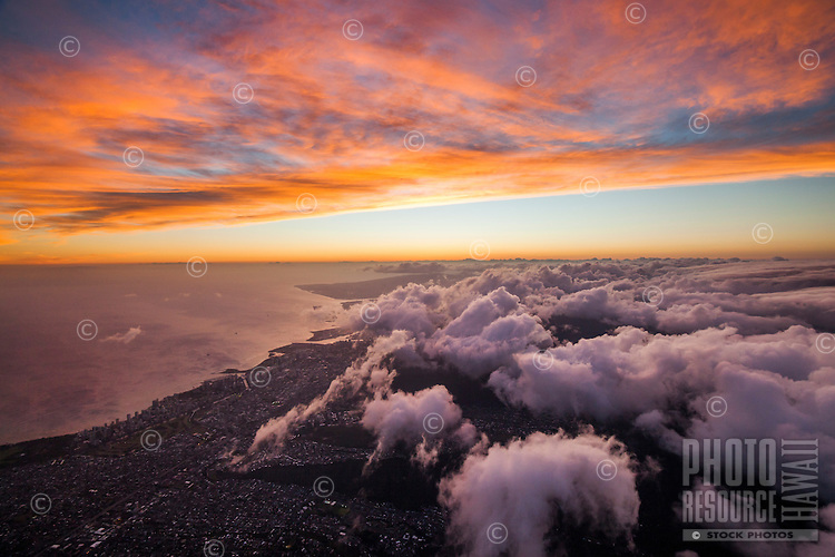 Clouds touched by the setting sun roll over Honolulu, O'ahu.