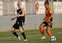 BOYDS, MARYLAND-JULY 07,2012:  Becky Sauerbrunn (11) of DC United Women slips the ball past Emilie Fillion (13) of Dayton Dutch Lions during a W League game at Maryland Soccerplex, in Boyds, Maryland. DC United women won 4-1.