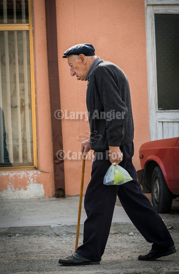 Street details of life in a small Serbian city..Man walking with a cain.