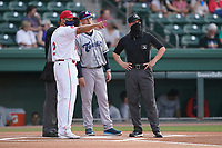 Asheville Tourists manager Nate Shaver meets with Greenville Drive manager Iggy Suarez and umpires Adam Pierce (partially hidden) and Jose Lozada before a game on Tuesday, June 1, 2021, at Fluor Field at the West End in Greenville, South Carolina. (Tom Priddy/Four Seam Images)