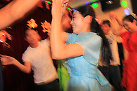 A North Korean waitress dances with Chinese tourists in a restaurant in the city of Dandong.