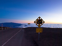 A cautionary road sign and cloud cover can still be seen at sunset at the top of Mauna Kea, island of Hawai'i.