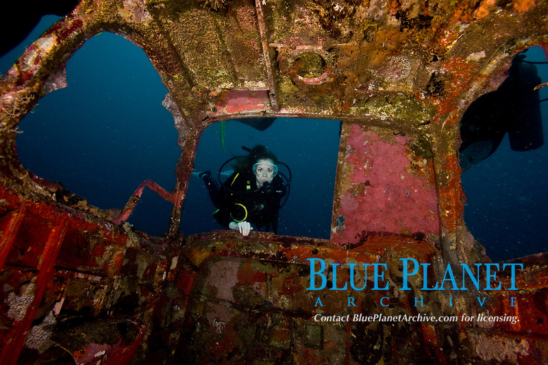 Diver entering the front window of a four seater plane wreck
