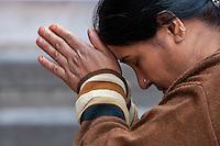 Nepal, Kathmandu.  Hindu Woman Praying at Base of Statue to Hindu God Hanuman.  Note the Nose Pin.