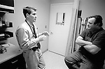 Young male doctor discussing symptoms with middle age male patient in examination room