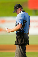 Home plate umpire Jake Wilburn checks his copy of the lineup during the South Atlantic League game between the Hickory Crawdads and the Kannapolis Intimidators at CMC-Northeast Stadium on July 28, 2013 in Kannapolis, North Carolina.  The Crawdads defeated the Intimidators 6-1.  (Brian Westerholt/Four Seam Images)