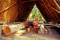 Hawaiian man carving a traditional Hawaiian sailing canoe at Puu Honua Honaunau, also known as city of refuge, a National historical park on the Big island