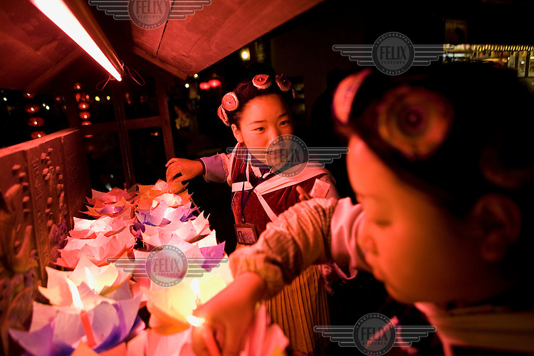 Two Nakhi (Naxi) girls selling candle trays to be placed and floated down the open canals of the old city of Lijiang, a centre of Nakhi culture which is a UNESCO World Heritage Site.