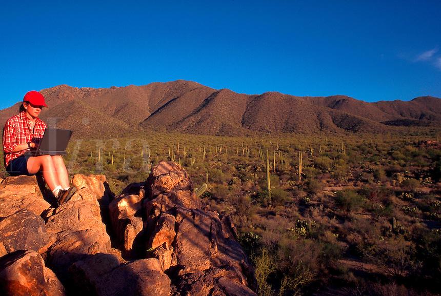 Girl using laptop in the desert