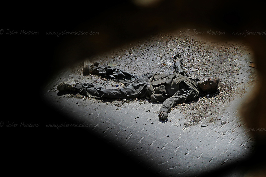 A Free Syria Army soldier lies dead after he was killed by a Free Syria Army sniper four weeks ago in the Salahaddin neighborhood of Aleppo. Bodies are often left where they lay because retrieving them might cost several lives as snipers from all sides would fire upon them. © Javier Manzano