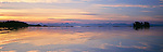 The waters of Chatham strait reflect and deepen the colors of sunset in Tongass National Forest in Southeast Alaska.