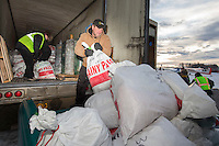 Volunteers move and sort straw, musher drop bags, people food and HEET to waitng Iditarod Air Force planes at the Willow, Alaska airport during the Food Flyout on Saturday, February 20, 2016.  Iditarod 2016