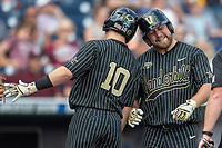 Vanderbilt Commodores outfielder Stephen Scott (19) celebrates with teammate Ethan Paul (10) after his second home run of the game against the Mississippi State Bulldogs in the NCAA College World Series on June 19, 2019 at TD Ameritrade Park in Omaha, Nebraska. Vanderbilt defeated Mississippi State 6-3. (Andrew Woolley/Four Seam Images)