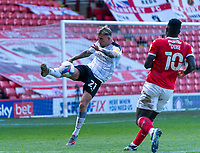 24th April 2021, Oakwell Stadium, Barnsley, Yorkshire, England; English Football League Championship Football, Barnsley FC versus Rotherham United; Angus MacDonald of Rotherham hooks clear under pressure from Daryl Dike of Barnsley