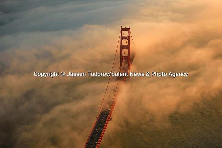 Pictured: Fog over Golden Gate Bridge in San Fransico, USA. <br /> <br /> Amazing aerial photos show off the majesty of America's landscape, its architecture, its industry and its wildlife.   From the startling blue potash pools of Utah to hundreds of aircraft sitting unused due to the pandemic, the images display a little seen side of the USA.<br /> <br /> Other images include a passenger plane plane as it touches down in California taken 4,500ft above it, fog over the Golden Gate Bridge and a solar farm in Nevada.   Professor of Music Jassen Todorov, from San Francisco, captured the striking pictures of the American West while flying in a light aircraft.   SEE OUR COPY FOR DETAILS<br /> <br /> Please byline: Jassen Todorov/Solent News<br /> <br /> © Jassen Todorov/Solent News & Photo Agency<br /> UK +44 (0) 2380 458800