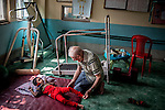 Father Laborde checks the condition of a child at Asha Neer,  who came there for physiotherapy. Howrah. West Bengal, India, Arindam Mukherjee/Agency Genesis