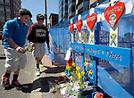 (Boston Ma 042014) Max Fairbank, 13, of Hampstead N.H. left and his brother Ben, 11, take a moment to remember the four deceased victims by adding flowers to a small memorial next to the finish line on Boylston Street in Boston Sunday, April 20, 2014, the day before the Boston Marathon. (Jim Michaud Photo) For Sunday