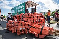 """Mit einer Demonstration unter dem Motto """"Seebruecke – Schafft sichere Haefen"""" zogen am Samstag den 7. Juli 2018 ueber 10.000 Menschen in Berlin zum Bundeskanzleramt. Sie forderten ein Ende der Kriminalisierung der zivilen Seenotrettung im Mittelmeer, wo Hilfsorganisationen wie Seawatch, Mission Lifeline, SOS Mediterrane Aerzte ohne Grenzen und Sea Eye Migranten aus Seenot retten. Diese Seenotrettungsorganisationen werden von mehreren europaeischen Staaten als """"Schlepper"""" diffamiert und ihre Schiffe beschlagnahmt. Anfang Juli wurde der Kapitaen der Lifeline von maltesischen Behoerden festgenommen.<br /> Die Seebruecke ist eine internationale Bewegung aus der Zivilbevoelkerung. Sie fordert """"sichere Fluchtwege, eine Entkriminalisierung der Seenotrettung und eine menschenwuerdige Aufnahme von gefluechteten Menschen. Wir wollen mehr Rettung statt weniger!"""".<br /> Zeitgleich fanden in mehrere deutschen Staedten Demonstrationen der """"Seebruecke"""" statt.<br /> Im Bild: Demonstranten stapeln Rettungswesten vor dem Bundeskanzleramt.<br /> 07.7.2018, Berlin<br /> Copyright: Christian-Ditsch.de<br /> [Inhaltsveraendernde Manipulation des Fotos nur nach ausdruecklicher Genehmigung des Fotografen. Vereinbarungen ueber Abtretung von Persoenlichkeitsrechten/Model Release der abgebildeten Person/Personen liegen nicht vor. NO MODEL RELEASE! Nur fuer Redaktionelle Zwecke. Don't publish without copyright Christian-Ditsch.de, Veroeffentlichung nur mit Fotografennennung, sowie gegen Honorar, MwSt. und Beleg. Konto: I N G - D i B a, IBAN DE58500105175400192269, BIC INGDDEFFXXX, Kontakt: post@christian-ditsch.de<br /> Bei der Bearbeitung der Dateiinformationen darf die Urheberkennzeichnung in den EXIF- und  IPTC-Daten nicht entfernt werden, diese sind in digitalen Medien nach §95c UrhG rechtlich geschuetzt. Der Urhebervermerk wird gemaess §13 UrhG verlangt.]"""