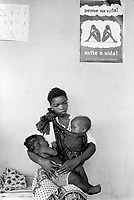 Mozambique. Province of Maputo. Maragra is a small village (80 km north of the capital Maputo). A mother and her two children are seated on a wood bench in the waiting room. They will be called for a medical consultation. On the wall is a poster about Aids, which says: Think about life, avoid Aids (sida). The drawing shows a couple, man and woman, back to back seated on the ground. They are thinking about the disease. The poster is part of a campaign of awareness on the HIV virus .The non governmental organisation (ngo) Médecins Sans Frontières (MSF) of Switzerland has rehabilitated the local clinic. © 1992 Didier Ruef