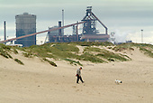 A man walks  with his dog on the beach close to the Corus steelworks, Redcar.