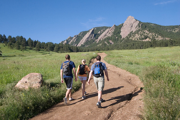Caucasian woman leading two Caucasian men hiking towards the Flatirons rock formation in Chautauqua Park, Boulder, Colorado, USA .  John leads private photo tours in Boulder and throughout Colorado. Year-round.