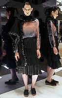 Model in Look 15: Black Melton Poncho, Ombre Sunrise Top, Black Flounce Skirt