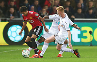 Jesse Lingard of Manchester United is challenged by Wayne Routledge of Swansea City and Sam Clucas during the Carabao Cup Fourth Round match between Swansea City and Manchester United at the Liberty Stadium, Swansea, Wales, UK. Tuesday 24 October 2017