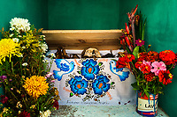"""A dried-up scull and bones are seen wrapped in a painted cloth and placed in a wooden crate inside a niche at the cemetery in Pomuch, Mexico, 26 October 2019. Every year on the Day of the Dead, people of Pomuch, a small Mayan community in the south of Mexico, visit the cemetery to take part in a pre-Hispanic tradition of cleaning of bones of their departed relatives (""""Limpia de huesos""""). People who die in Pomuch are firstly buried for three years in an above-ground tomb then the dried-up bodies are taken out, bones are separated, wrapped in a decorated cloth, put into a wooden crate, and placed on display among flowers for veneration."""