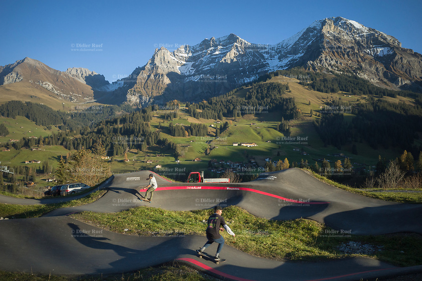 """Switzerland. Canton Bern. Adelboden. Two men enjoy the skatepark in the late afternoon. View on the Gross Lohner (also spelled Gross Loner: Great Lohner),which is a limestone mountain of the Bernese Alps, located in the Bernese Oberland. The main summit has an elevation of 3,048.7 metres and is distinguished by the name Vorder Lohner (""""Fore Lohner""""). The mountain features several other peaks, from east to west: Nünihorn, 2,717 metres , Hinder Lohner (Rear Lohner), 2,929 metres, Mittler Lohner (Central Lohner), 3,002 metres and Mittaghorn, 2,678 metres. The Lohner range is located east of Adelboden in the Engstlige valley. The Gross Lohner is separated from the Chlyne Lohner (Small Lohner) to the north by the Bunderchrinde Pass. Adelboden is a mountain village and a municipality located in the Frutigen-Niedersimmental administrative district in the Bernese Highlands. 6.11.2020 © 2020 Didier Ruef"""