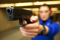 Switzerland. Geneva. A female police officer is aiming her Glock hand gun at firing range. The policewoman is traing at the Police education center (Centre de formation de la Police. CCFP). The picture is looking down the barrel of a Glock pistol which is a semi-automatic pistol designed and produced by Glock Ges.m.b.H. Glock was the firts to introduce ferritic nitrocarburizing into the firearms industry as an anti-corrosion surface treatment for metal gun parts. 22.03.12 © 2012 Didier Ruef