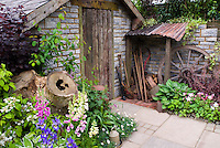 Rustic old farm tools, country style garden, ornaments, old brick shed, patio, wall, charming old fashioned feel to the garden mixed with vegetables, flowers, iris, Digitalis, Viburnum shrubs, Heuchera in flower, lettuce, herbs, vines, wagon wheel . Board and batten door