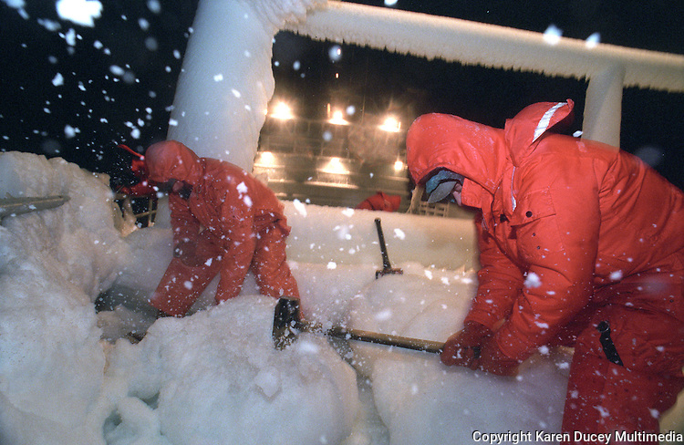 """Crewmen beat ice off the bow of the fishing vessel """"Kiska Sea"""" during an opilio crab fishing season in the the Bering Sea in January and February of 1995.  Ice is formed when waves crash over the bow and freeze immediately to anything they touch.  Several feet of ice had covered the boat in just a matter of hours during this storm.  The Bering Sea is known for having the worst storms in the world.  Nights are long and cold in the arctic in the winter.  Crab fishing in the Bering Sea is considered to be one of the most dangerous jobs in the world.  This fishery is managed by the Alaska Department of Fish and Game and is a sustainable fishery.  The Discovery Channel produced a TV series called """"The Deadliest Catch"""" which popularized this fishery."""