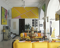 Modern art dominates the walls and ceiling of the spacious living room, but does not prevent it from being a homely space