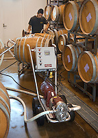 Winery worker pumps the grape juice from one OAK BARREL to another to remove sediment at JOULLIAN VINEYARDS - CARMEL VALLEY, CALIFORNIA MR