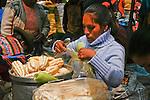 A Peruvian women bags corn at the Pisac market.