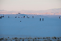 People watch the sunset at White Sands National Monument near Alamogordo, New Mexico, USA, on Sat., Dec. 30, 2017.