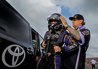 Aug 31, 2014; Clermont, IN, USA; NHRA funny car driver Alexis DeJoria (left) is assisted with putting on her safety gear by husband, television personality Jesse James during qualifying for the US Nationals at Lucas Oil Raceway. Mandatory Credit: Mark J. Rebilas-USA TODAY Sports