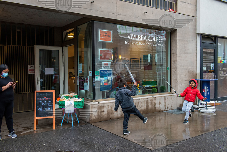The owner's children play outside a Filipino-owned cafe, in the Paquis district, which is offfering free sandwiches as part of an effort to support people in need, in part due to financial problems due to the coronavirus pandemic.