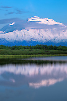 Mount McKinley, the tallest mountain in the United States at 20,320' reflects at midnight in Reflection Pond.  Denali National Park, Alaska.  Details of the landscape are preserved using HDR processing.