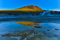 El Tatio geyser field (4320m), largest in Southern Hemisphere, highest in the world, at sunrise with vivid mountain reflections, Atacama Desert Chile