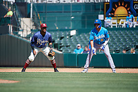 Frisco RoughRiders first baseman Andretty Cordeo (4) holds Hudson Potts (10) on during a Texas League game against the Amarillo Sod Poodles on May 19, 2019 at Dr Pepper Ballpark in Frisco, Texas.  (Mike Augustin/Four Seam Images)