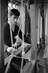 Hand weaving traditional fly and shuttle flying shuttle hand loom. West coast Ireland Eire County Kerry, boy weaving in family run textile business. 1969 1960s