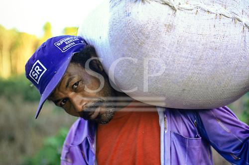 "Juruena, Amazon, Brazil. Settler carrying a large sack on his shoulder, wearing a blue ""Supermercado Ranzan"" cap."