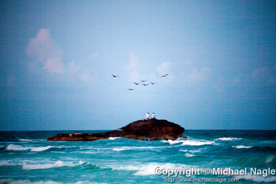 TULUM, MEXICO - APRIL 30, 2009: Fisherman and birds look for fish at dusk on April 30, 2009 in Tulum, Mexico.  (PHOTOGRAPH BY MICHAEL NAGLE)