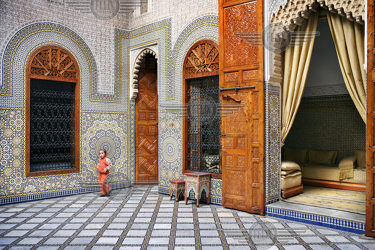 A child walks through the the internal courtyard of a renovated riyad, in the medina of Rabat, that is decorated with ornate mosaic designs. It is now rented out for parties and receptions.
