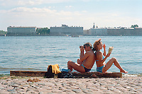 Saint Petersburg, Russia, June 2002..Sunbathing by the walls of the Peter Paul Fortress.The mid-summer White Nights period when the sun sets only briefly is a time of festivals, entertainment and walks along the Neva River to watch the city bridges raise for shipping..