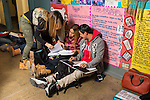 High school students studying and interacting in corridor during lunch break.